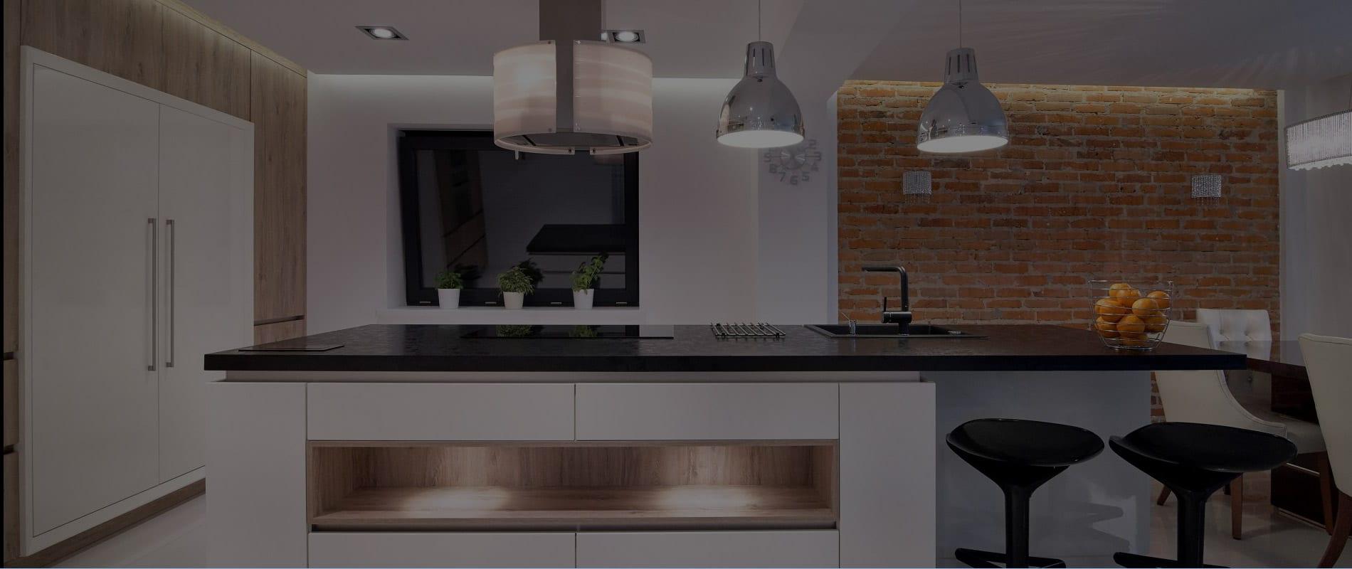 Sleek custom kitchen design with black counter tops, underneath counter lighting